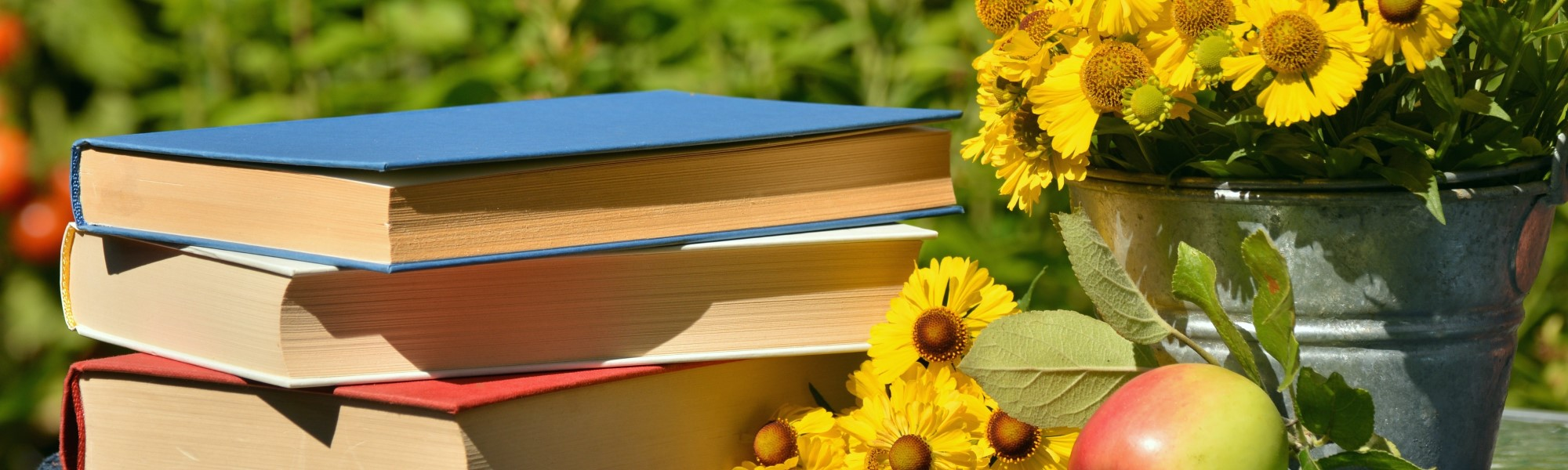 books in grass with flowers
