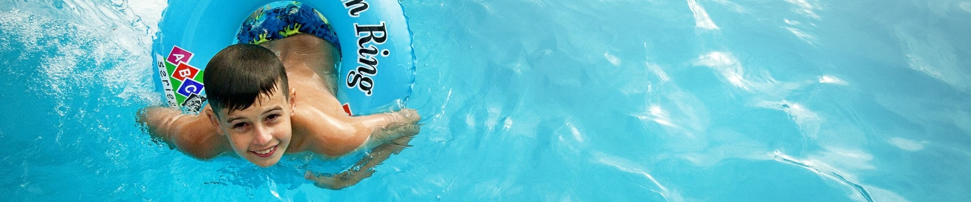 child swimming with a tube in the pool